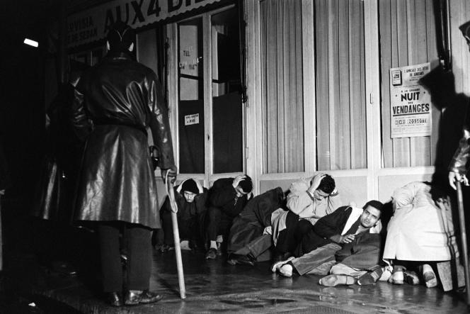 (FILES) In this file photo taken on October 17, 1961 Algerian demonstrators arrested in Puteaux, west of Paris, during the peaceful demonstration wait with their hands above their heads to be questionned under police surveillance, during the Algerian war. Sixty years ago, on October 17, 1961, 30,000 Algerians who had come to demonstrate peacefully in Paris were subjected to violent repression. Official assessment: three dead and sixty wounded, very far from reality according to historians. (Photo by Fernand PARIZOT / AFP)